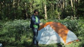 通过selfie棍子供以人员在您的电话的照片 附近的立场一个帐篷在森林,清早里 股票录像