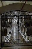 通过wrought-iron金属门您能看到有连续说谎老橡木的桶的葡萄酒库 免版税库存图片