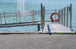 通道,从岸的下降到残疾的水 库存照片