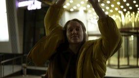 通风地跳舞在夜街道上的无忧无虑的微笑的女性 摇她的有短的金发的头 影视素材