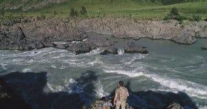 通风 旅客在山河附近接近峭壁的边缘 鸟瞰图 旅客家庭有孩子的 股票录像
