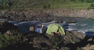 通风 旅客家庭有孩子的在帐篷附近坐并且享受山河和山的看法 股票录像
