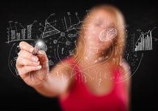 速写图表和图的俏丽的女孩在墙壁 免版税库存图片