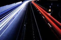 速度交通-光在机动车路高速公路落后在晚上,长期 库存照片