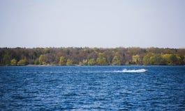 速度在天蓝色的湖的汽船 库存照片