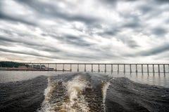 速度小船踪影在蓝色海水的在马瑙斯,巴西 与桥梁的海景在多云天空的天际 旅行和假期 A 免版税库存图片
