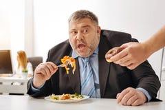 速食被诱惑的可笑松的人 库存照片