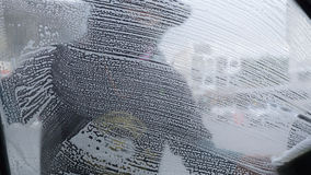 仿造在汽车玻璃的肥皂,当洗涤汽车的一个人,采取从 免版税库存照片