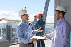 建造场所会议签署的合同愉快微笑的两个修造的商人 免版税库存图片
