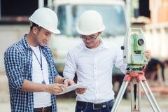 建造场所和A的土木工程师登陆使用a的测量员 免版税库存照片