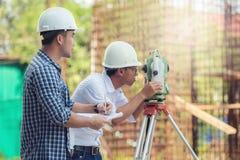 建造场所和A的土木工程师登陆使用a的测量员 库存图片