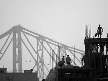 建造场所工作者有豪拉桥梁背景 免版税图库摄影