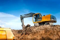 建造场所挖掘者、挖掘机和倾销者卡车 行业 免版税库存图片