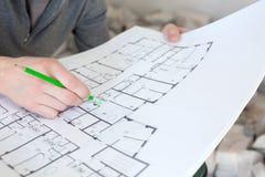 建造场所检查文件的一名建筑工人 免版税库存照片