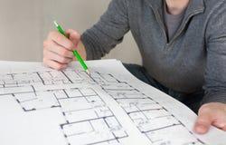 建造场所检查文件的一名建筑工人 免版税库存图片