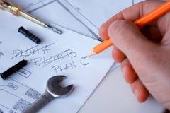 建造场所检查新的计划的一名建筑工人 图库摄影