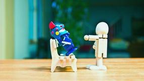造成对机器人的威胁坐长凳的一个木玩偶 免版税库存照片