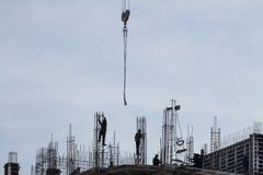建造者剪影在大厦顶部的在有蓝天的建造场所 库存图片