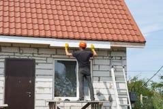建造者在屋顶运作 免版税库存照片