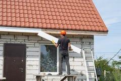 建造者在屋顶运作 库存照片