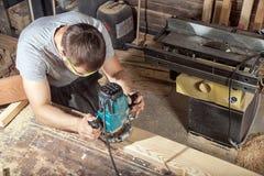 建造者处理与一台铣床的一个木板条 库存照片