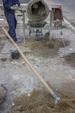 建造者工作者混合的水泥,在第一个计划的铁锹 库存照片