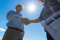 建造者握手,建筑师和承包商协议在谈论的会议期间图纸在建筑的Buiding计划 图库摄影