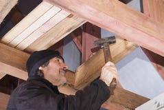 建造者锤击一个钉子 库存照片