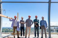 建造者队在Costruction站点的,在安全帽户外合作和配合概念的愉快的微笑的工头小组 免版税图库摄影