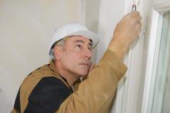 建造者驾驶螺丝入与螺丝刀的天花板纤维板 免版税库存图片