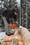 建造者整理与锯,锯木屑飞行的一本日志 免版税图库摄影