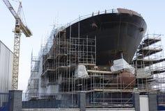 造船过程中与在口岸格拉斯哥,由仍然被架设的海脚手架的苏格兰的起重机 免版税库存照片