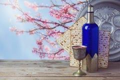 逾越节未发酵的面包和酒在木葡萄酒桌上在开花树背景 免版税库存照片
