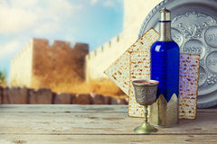 逾越节未发酵的面包和酒在木葡萄酒桌上在老城市墙壁 有西伯来文本的塞德板材 免版税图库摄影