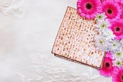 逾越节背景 在白色桌布的发酵的硬面(犹太逾越节面包)和花 库存照片
