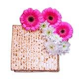 逾越节背景 在白色隔绝的发酵的硬面(犹太逾越节面包)和花 免版税图库摄影