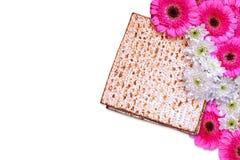 逾越节背景 在白色隔绝的发酵的硬面(犹太逾越节面包)和花 库存照片