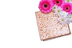 逾越节背景 在白色隔绝的发酵的硬面(犹太逾越节面包)和花 库存图片