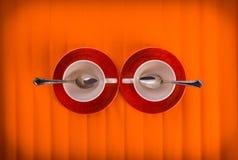 遇见两个白色空的杯子用茶在橙色颜色背景的红色板材从上面捞出,看法 库存图片