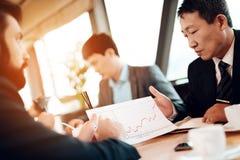 遇见中国商人在餐馆 他们谈论企业图表 免版税库存图片