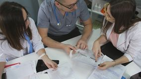 遇见医生桌的办公室诊所 人医生和两位妇女医生与在的文件一起使用 影视素材