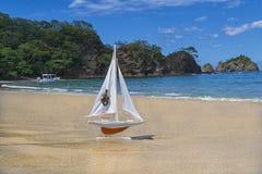 遇见在一个美丽的海滩的冒险的玩具橙色船风帆 免版税库存图片