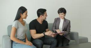 遇见房地产经纪人,同女性经纪的签署的合同的年轻有吸引力的夫妇 股票录像