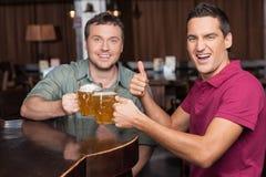 遇见朋友的早晨好。拿着杯子与的两个愉快的朋友 库存图片