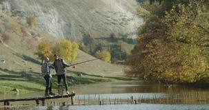 遇见的两个朋友除一个美丽的湖以外在开始对钓鱼前喝有些瓶水的他们 股票视频