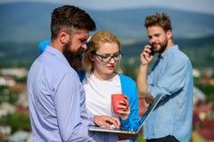 遇见非正式大气的商务伙伴 同事支付注意屏幕膝上型计算机,当人谈的电话时 免版税库存照片