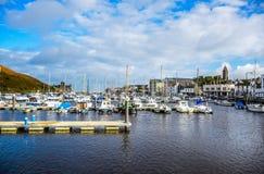 道格拉斯,曼岛- 10月17 :乘快艇相接在一个好的小口岸的海湾在一清楚的蓝天天在道格一个小镇  库存照片
