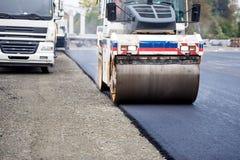 道路工程,涂柏油和放置新鲜的沥清在建筑工作期间 工业重的压紧机 免版税库存图片