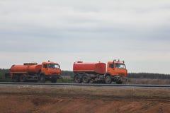 道路施工工作-在高速公路的两辆红色浇灌的卡车在领域中 图库摄影