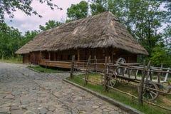 道路标示用导致有一个茅屋顶和一辆装饰木独轮车的一个老乌克兰房子的石瓦片 免版税库存图片